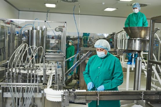 Crew in PPE monitoring an assembly line in a clean room