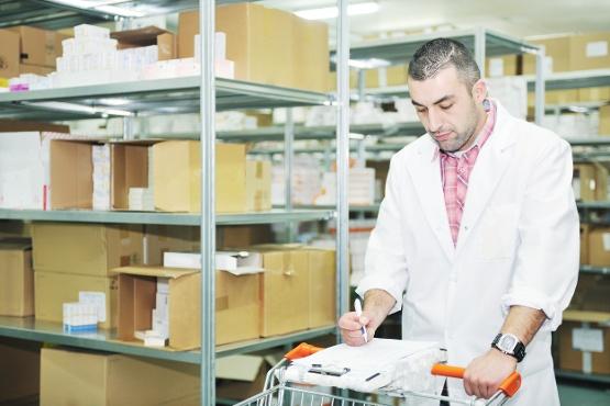 Man in lab coat marking off checklist in warehouse